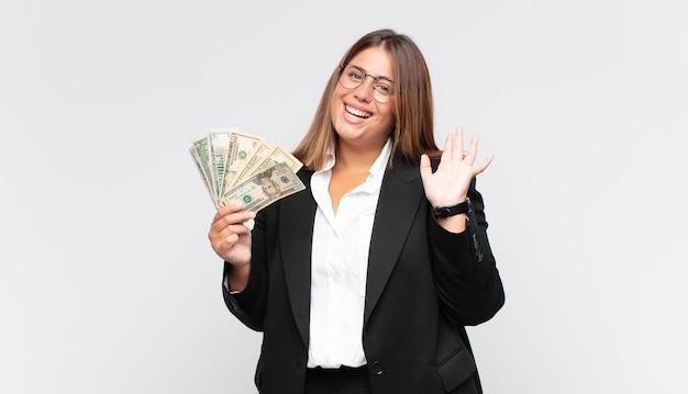 Giovane donna con banconote che sorride allegramente e allegramente, agitando la mano, dandoti il benvenuto e salutandoti o salutandoti