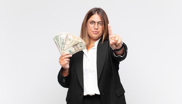 Giovane donna con le banconote sorridendo e guardando amichevole, mostrando il numero uno o il primo con la mano in avanti, conto alla rovescia