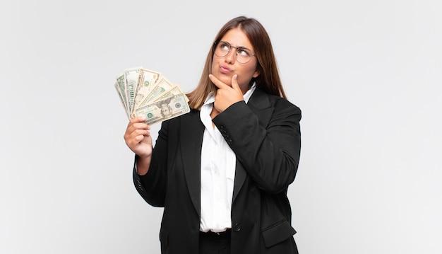 Giovane donna con banconote pensando, sentendosi dubbiosa e confusa, con diverse opzioni, chiedendosi quale decisione prendere