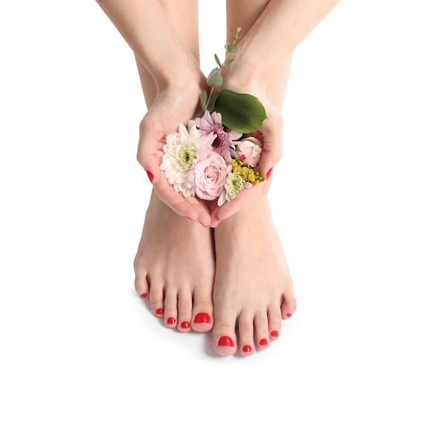 Giovane donna con bella pedicure e fiori su bianco