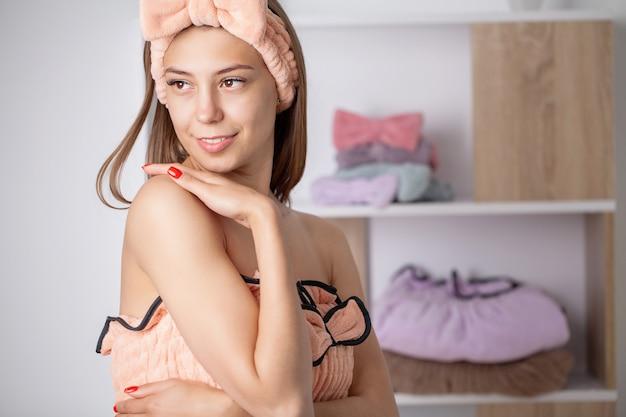 Giovane donna con una bella pelle in un accappatoio in un appartamento domestico