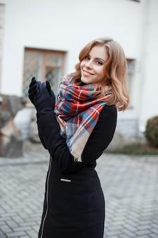 Giovane donna con un bel sorriso in un cappotto invernale in guanti neri con una sciarpa di lana alla moda in posa all'aperto