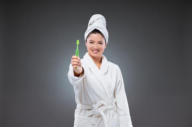 Una giovane donna con bellissimi denti bianchi in un accappatoio e con un asciugamano avvolto intorno alla testa dopo il bagno tiene uno spazzolino da denti in mano e lo mostra