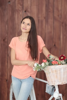 Giovane donna con bicicletta e fiori di primavera in un cesto