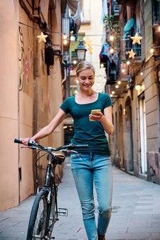Giovane donna con la bici che usa il suo smartphone mentre cammina