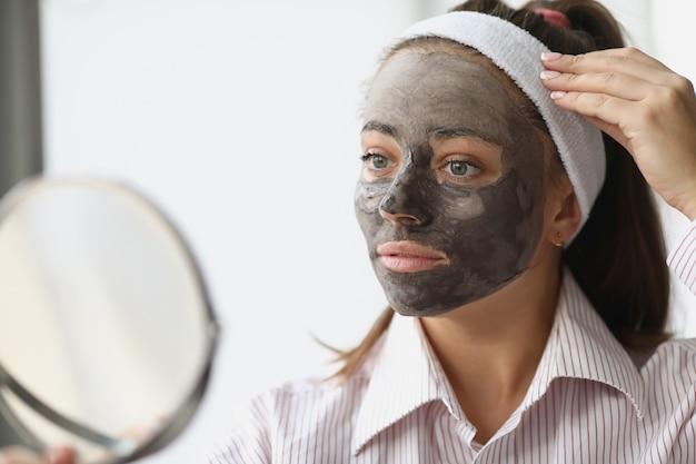 Giovane donna con maschera di argilla nera che si guarda allo specchio a casa