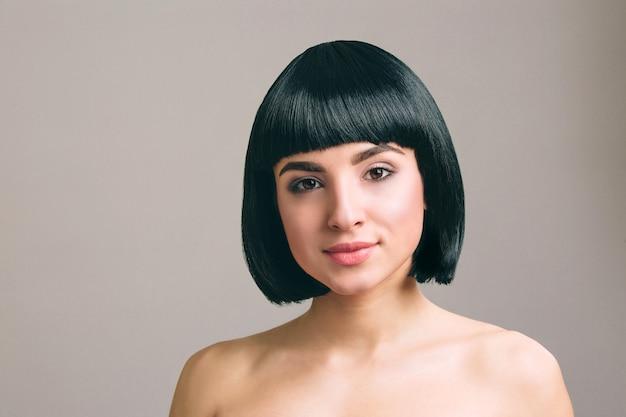 Giovane donna con i capelli neri in posa. isolato su sfondo chiaro taglio di capelli bob.