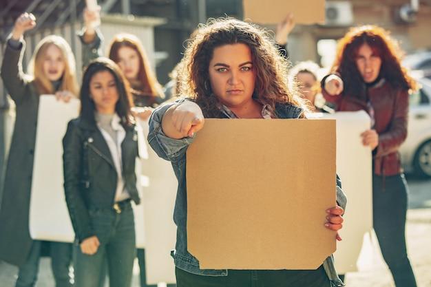 Giovane donna con poster in bianco di fronte a persone che protestano per i diritti delle donne e l'uguaglianza per strada. incontro su problemi sul posto di lavoro, pressioni maschili, abusi domestici, molestie. copyspace.