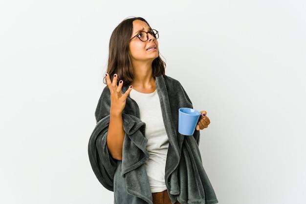 Giovane donna con una coperta isolata sul muro bianco che grida al cielo, alzando lo sguardo, frustrato
