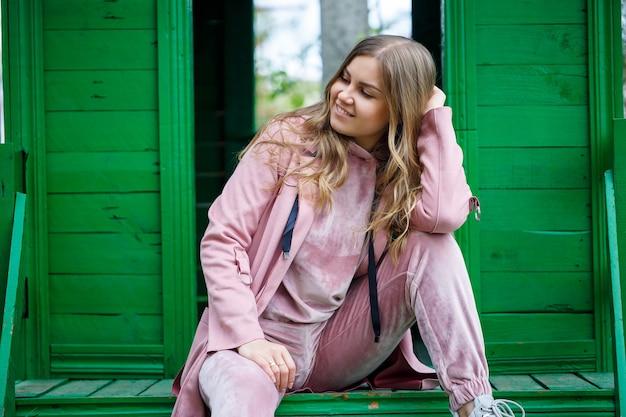 Una giovane donna dai capelli biondi di aspetto europeo siede sui gradini. ragazza in abito rosa e scarpe da ginnastica