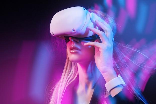 La giovane donna con i capelli biondi in un casco vr si guarda intorno con sorpresa e gioia