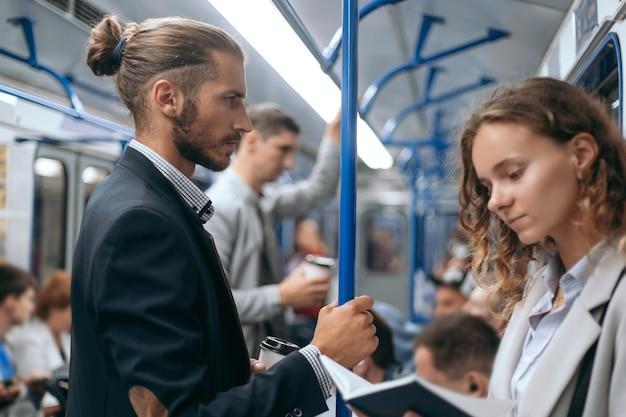 Giovane donna con un libro in piedi su un treno della metropolitana