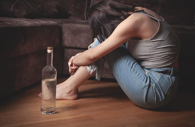 Giovane donna con una bottiglia di vodka a casa.