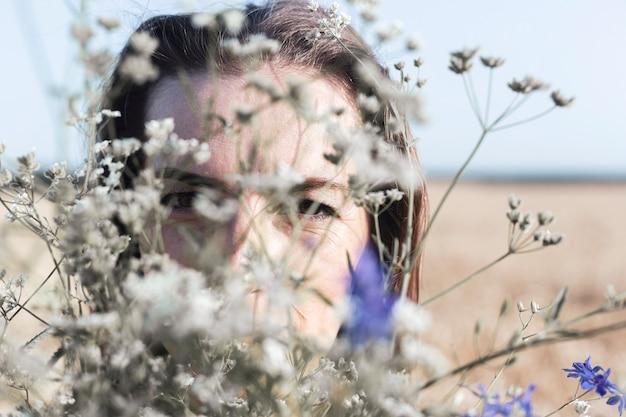 Giovane donna con un mazzo di fiori selvatici nel campo.