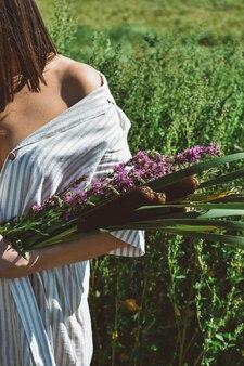 Giovane donna con un bouquet di fiori selvatici rilassante in un giardino