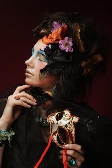 Giovane donna con trucco luminoso con maschera carnevale