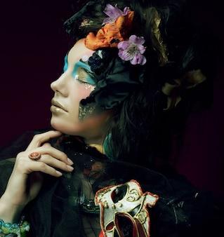 Giovane donna con trucco luminoso con maschera di carnevale