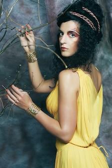 Giovane donna con trucco luminoso con rami secchi