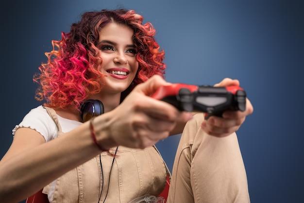 Giovane donna con i capelli ricci di colore rosso brillante che gioca video gioco.