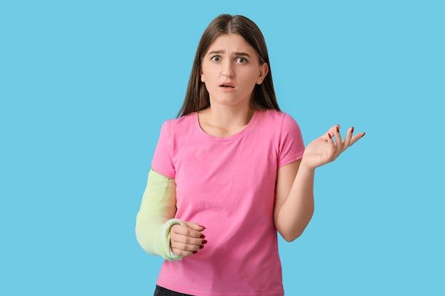 Giovane donna con il braccio rotto sul colore