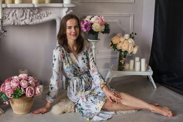 Giovane donna con i capelli castani in un abito floreale seduta sul pavimento tra molti vasi di fiori con colori diversi nella stanza bianca. atmosfera primaverile. ritratto di una ragazza elegante circondata da candele.