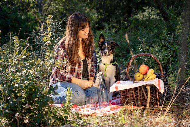 Giovane donna con i capelli castani e la pelle chiara su un picnic con il suo cucciolo di border collie e un cesto di vimini con frutta, priorità bassa della foresta mediterranea e ragazza sorride felice