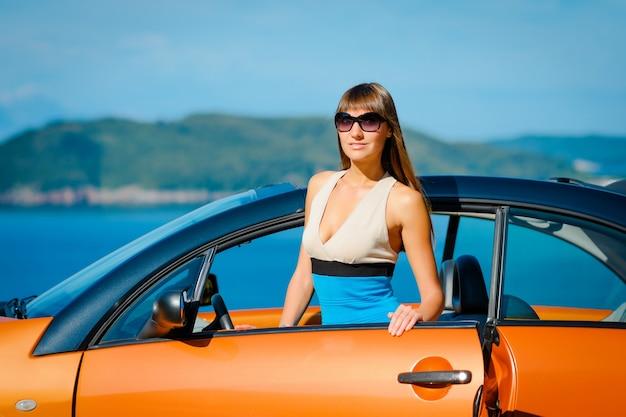 Giovane donna con auto sul lato mare