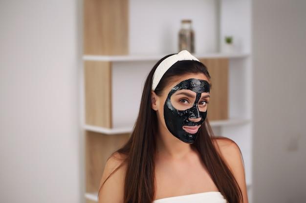 Giovane donna con maschera nera detox al carbonio sul viso, ragazza adolescente si prende cura della pelle grassa