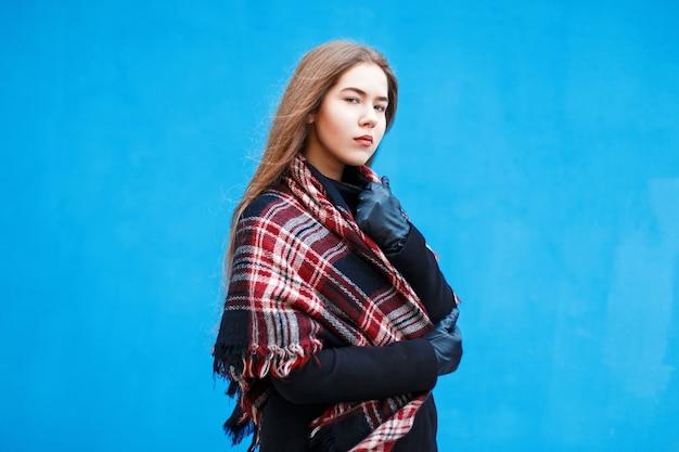 Giovane donna con una sciarpa rossa a scacchi vicino a un muro blu