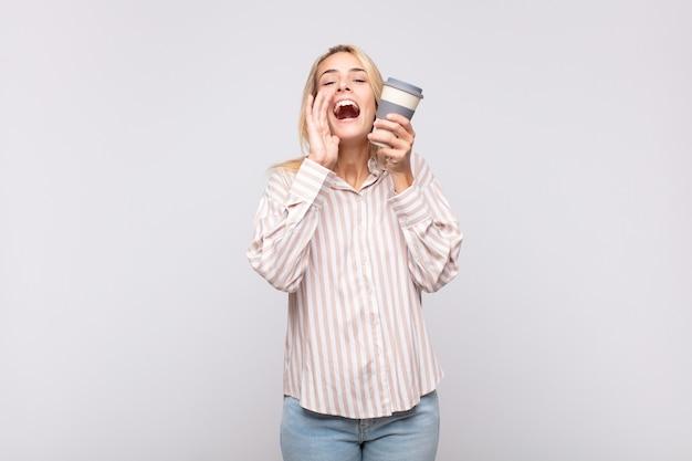 Giovane donna con un caffè che si sente felice, eccitata e positiva, dando un grande grido con le mani vicino alla bocca, chiamando