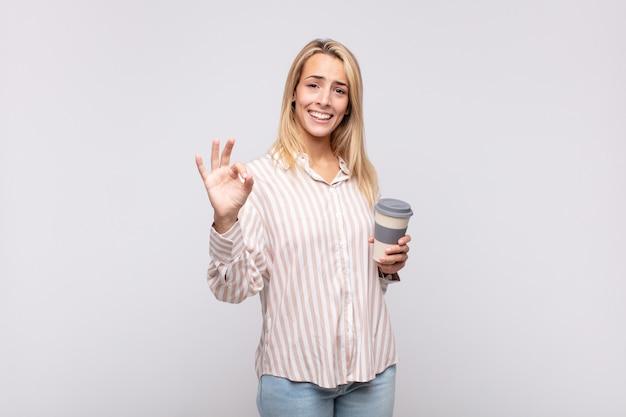 Giovane donna con un caffè che si sente felice, rilassata e soddisfatta, mostrando l'approvazione con il gesto giusto, sorridendo