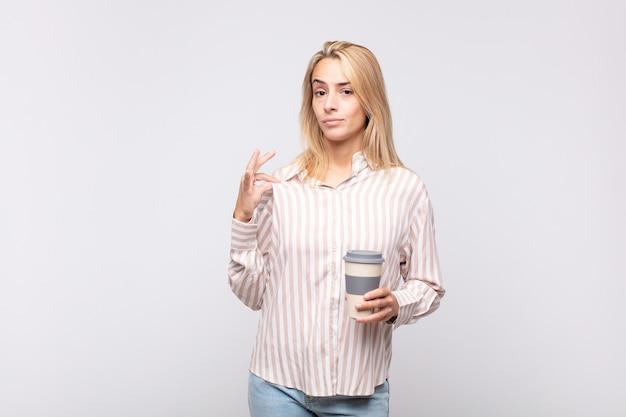 Giovane donna con un caffè che sembra arrogante, di successo, positiva e orgogliosa, indicando se stessa