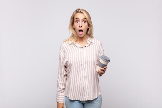 Giovane donna con un caffè che sembra molto scioccata o sorpresa, fissando con la bocca aperta dicendo wow