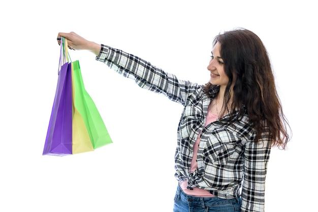 Giovane donna con borse della spesa colorate isolato sul muro bianco