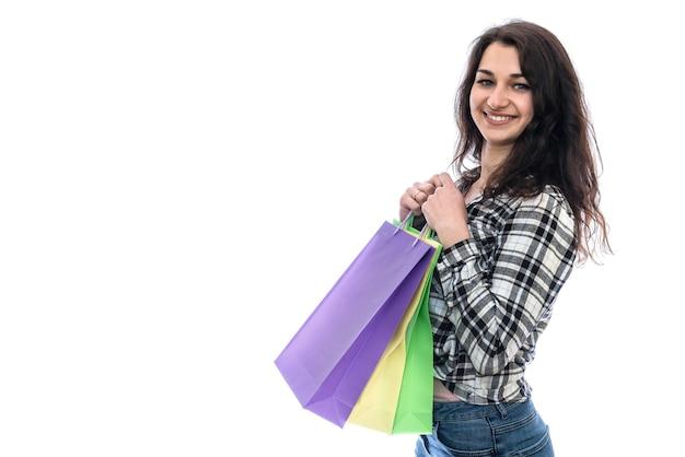 Giovane donna con sacchetti della spesa colorati isolati su bianco