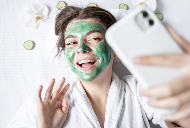 La giovane donna con una maschera cosmetica sul viso fa un selfie su uno smartphone