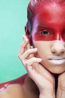 Giovane donna con arte creativa del viso su sfondo verde