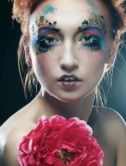 Giovane donna con trucco creativo che tiene grande fiore rosa