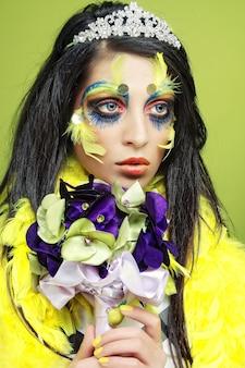 Giovane donna con trucco creativo che tiene un mazzo di gioielli