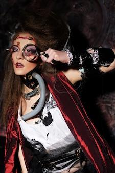 Giovane donna con trucco creativo che tiene una lente d'ingrandimento