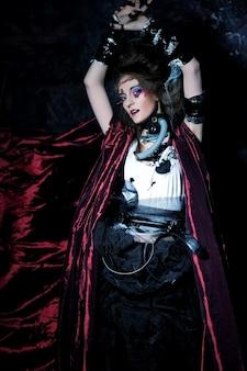 Giovane donna con trucco creativo in un impermeabile rosso. tema di halloween. tema degli zombi.