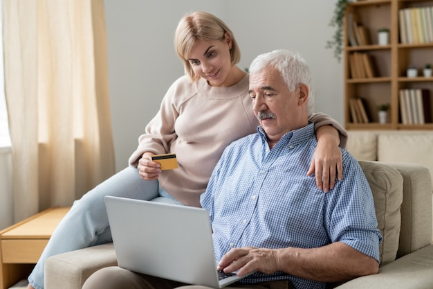 Giovane donna con carta di credito che abbraccia il suo padre senior con il laptop mentre entrambi lo shopping online sul divano di casa