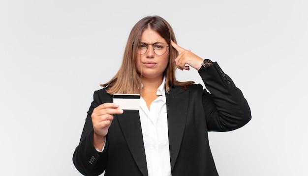 Giovane donna con una carta di credito che si sente confusa e perplessa, dimostrando che sei pazzo, pazzo o fuori di testa