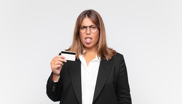 Giovane donna con una carta di credito che si sente disgustata e irritata, sporge la lingua, non gli piace qualcosa di brutto e schifoso