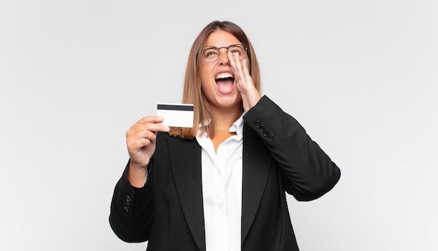 Giovane donna con una carta di credito che si sente felice, eccitata e positiva, facendo un grande grido con le mani vicino alla bocca, chiamando
