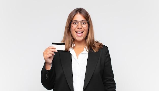 Giovane donna con una carta di credito che sembra felice e piacevolmente sorpresa