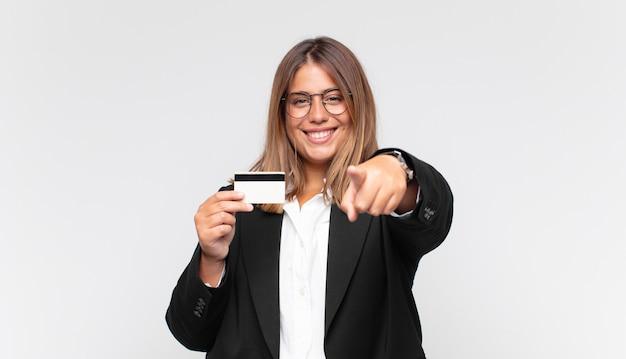 Giovane donna con una carta di credito che punta alla telecamera con un sorriso soddisfatto, fiducioso, amichevole, scegliendo te