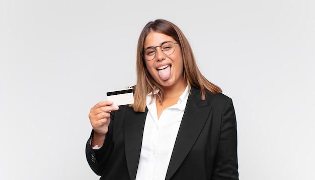 Giovane donna con una carta di credito con atteggiamento allegro, spensierato, ribelle, scherzando e con la lingua fuori, divertendosi