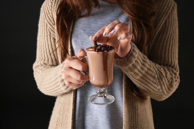 Giovane donna con una tazza di gustosa bevanda al cacao su sfondo nero, primo piano