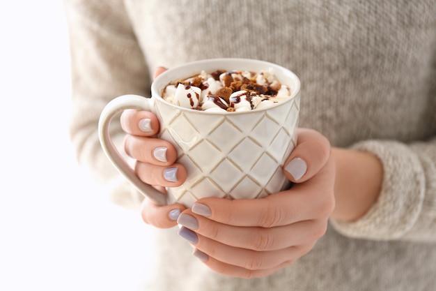 Giovane donna con una tazza di gustosa bevanda al cacao, primo piano